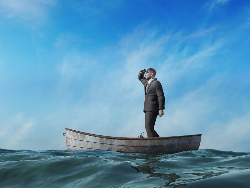 Businessman standing on boat looking out to the distance for help