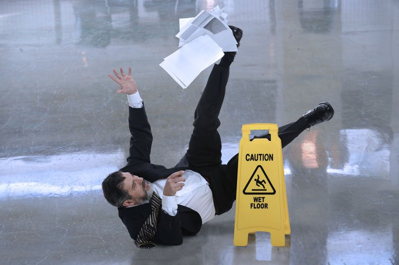 Photo d'un homme d'affaires glissant sur un plancher mouillé avec des documents entre les mains.