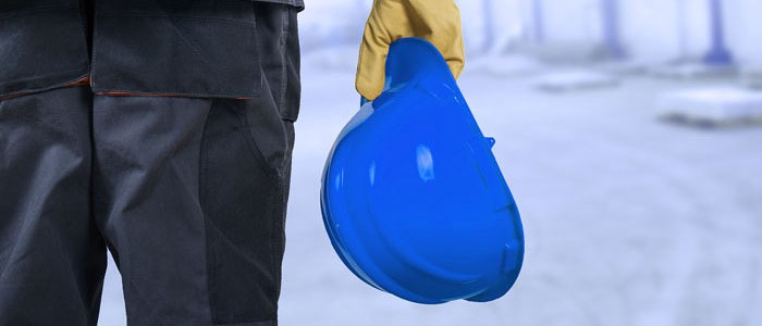 Construction worker holding a blue safety helmet