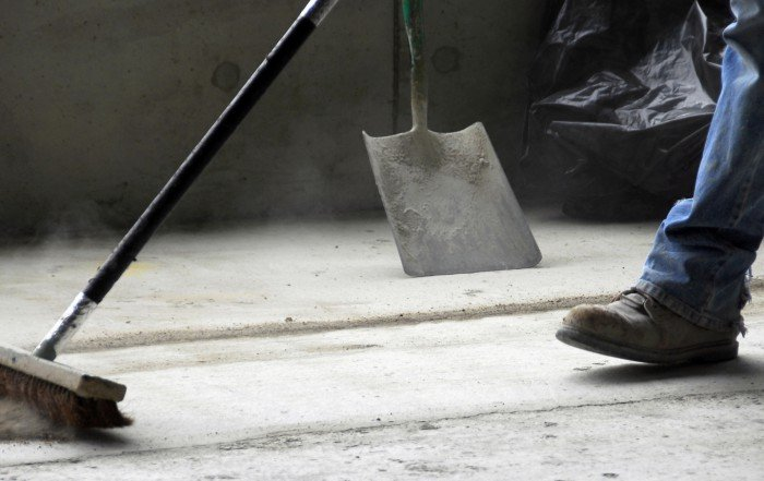 A construction worker sweeping.