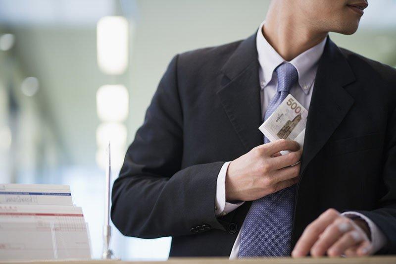 Photo d'un employé volant de l'argent à son entreprise.