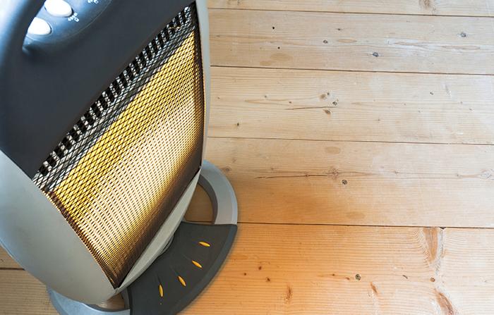 Photo en plongée d'un appareil de chauffage placé sur un plancher de bois.