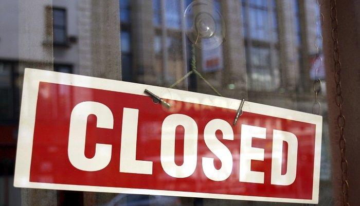 Photo d'une affiche rouge et blanche dans la fenêtre d'une boutique indiquant qu'elle est fermée.