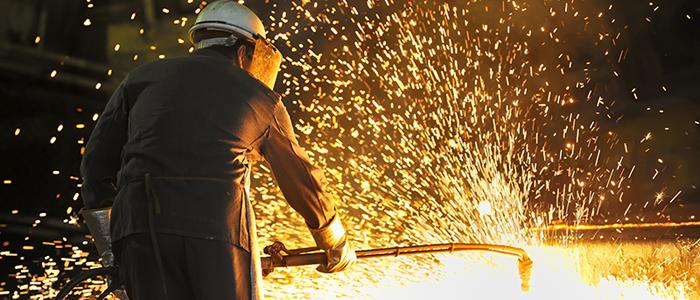 Photo d'un travailleur soudant du métal avec des étincelles jaillissant autour de lui.