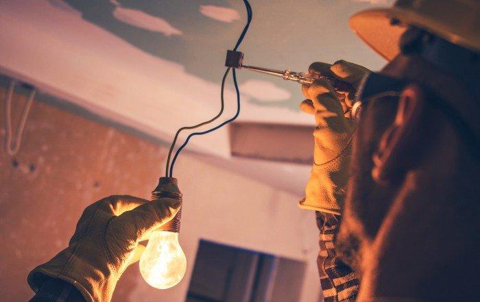Photo d'un entrepreneur en électricité portant de l'équipement de protection et réparant les fils d'un luminaire.