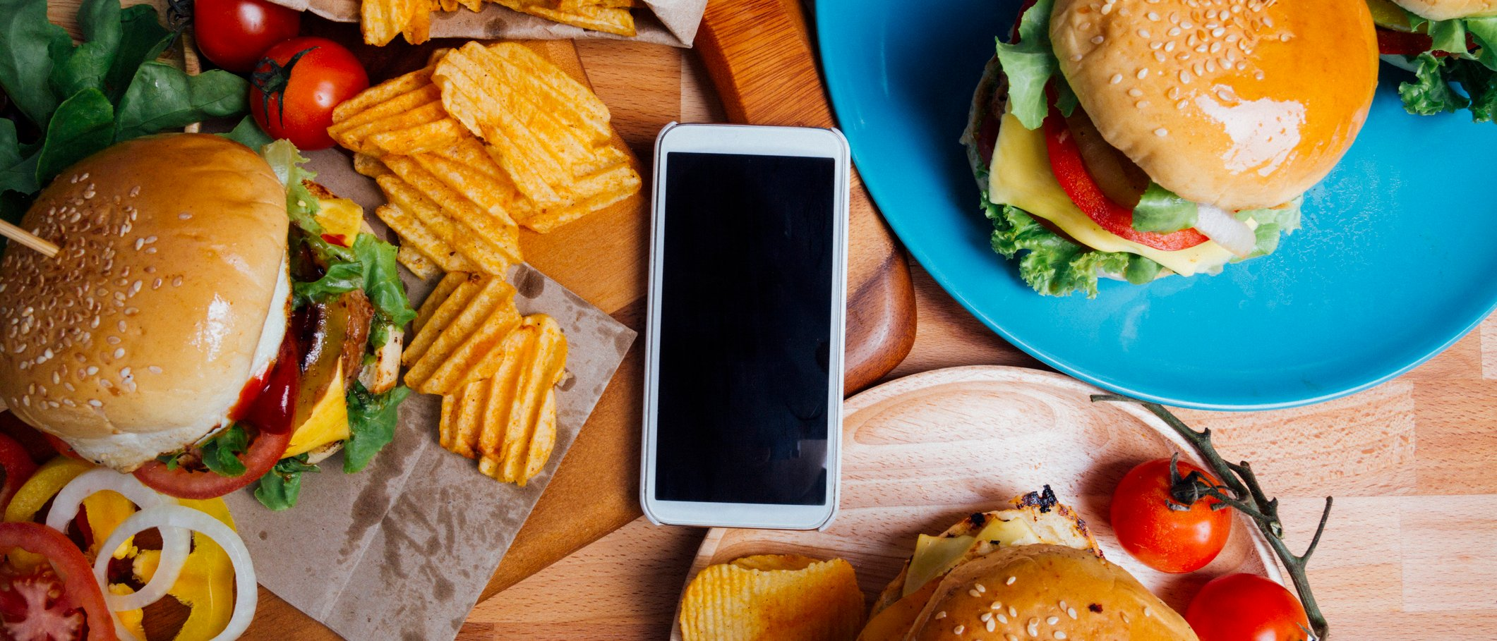 Cell phone placed in middle of a restaurant table surrounded by burgers and fries.