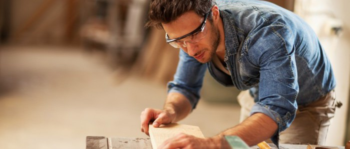 Male contractor working with tech tools while cutting wood