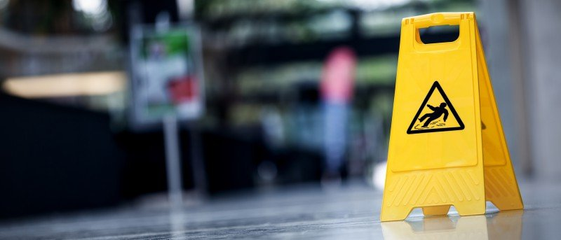 Photo d'une affiche jaune indiquant que le plancher est mouillé afin d'éviter les chutes.