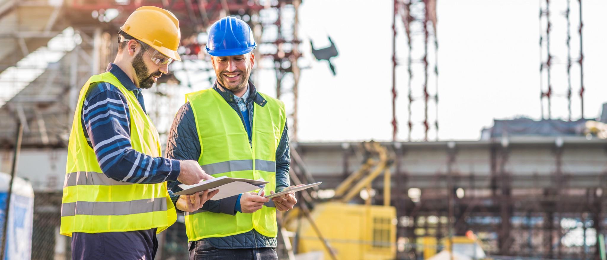 Photo de deux travailleurs de la construction discutant de plans d'affaires.