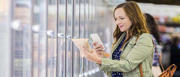 Photo d'une cliente utilisant une application sur son téléphone intelligent pour faire son épicerie plus facilement.