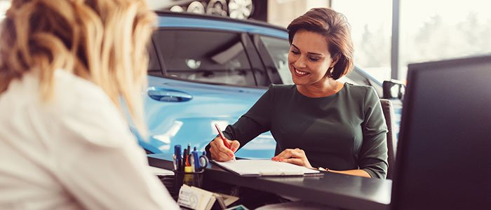Female auto dealer selling car to client
