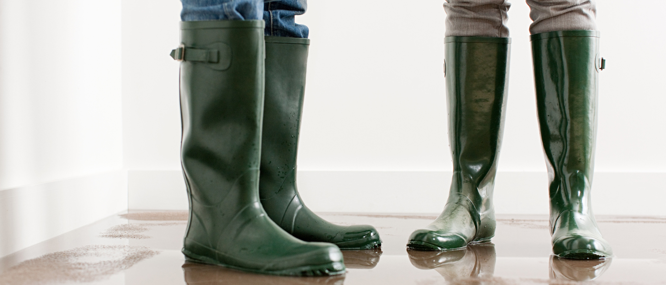 Close up of two people wearing green rubber rain boots