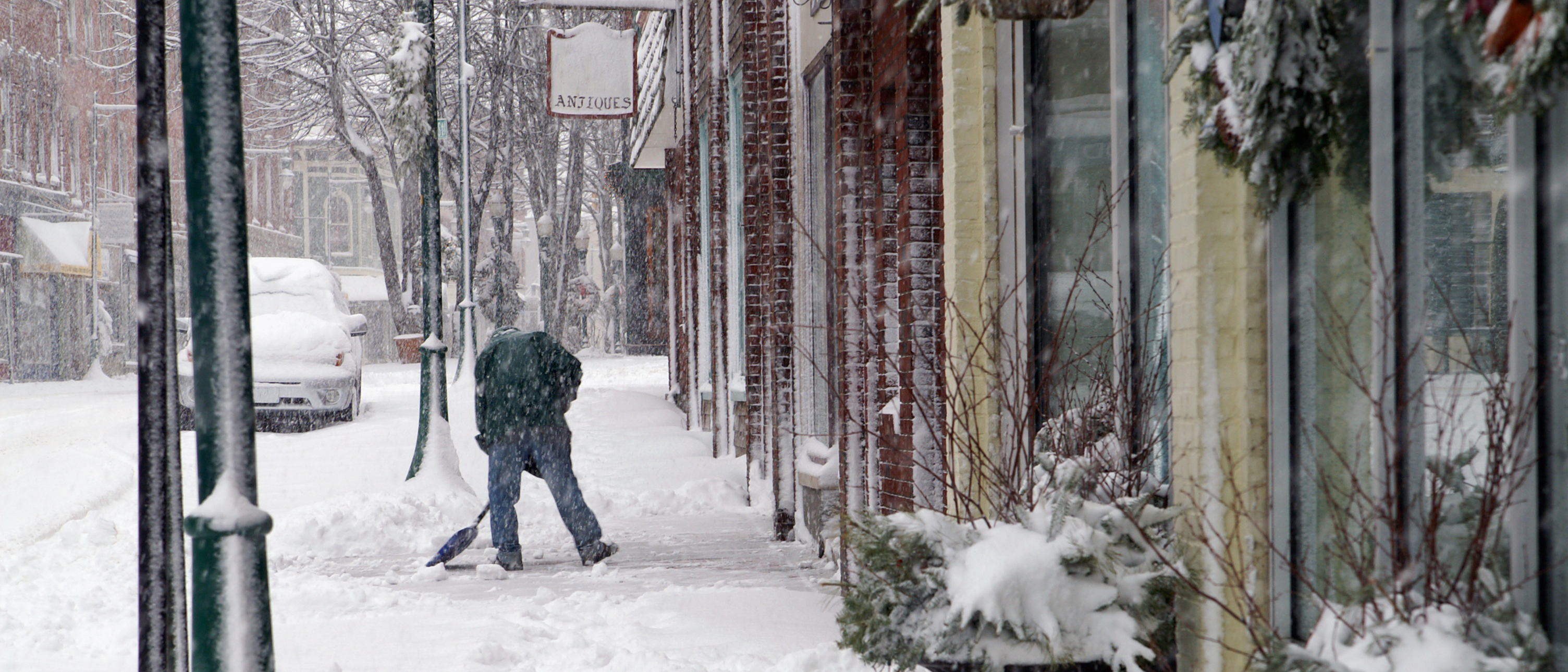 Business owner shovelling snow in front of his shop