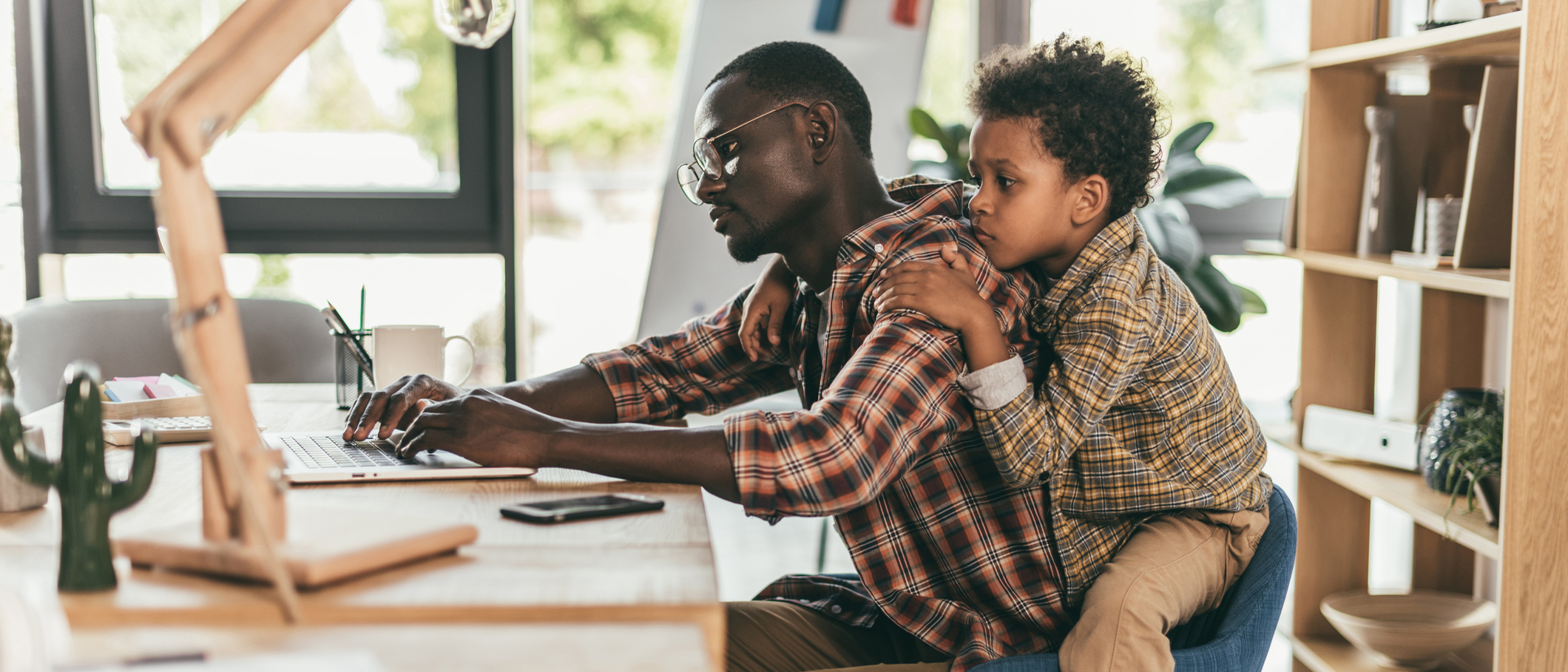 Man working from home while taking care of his son