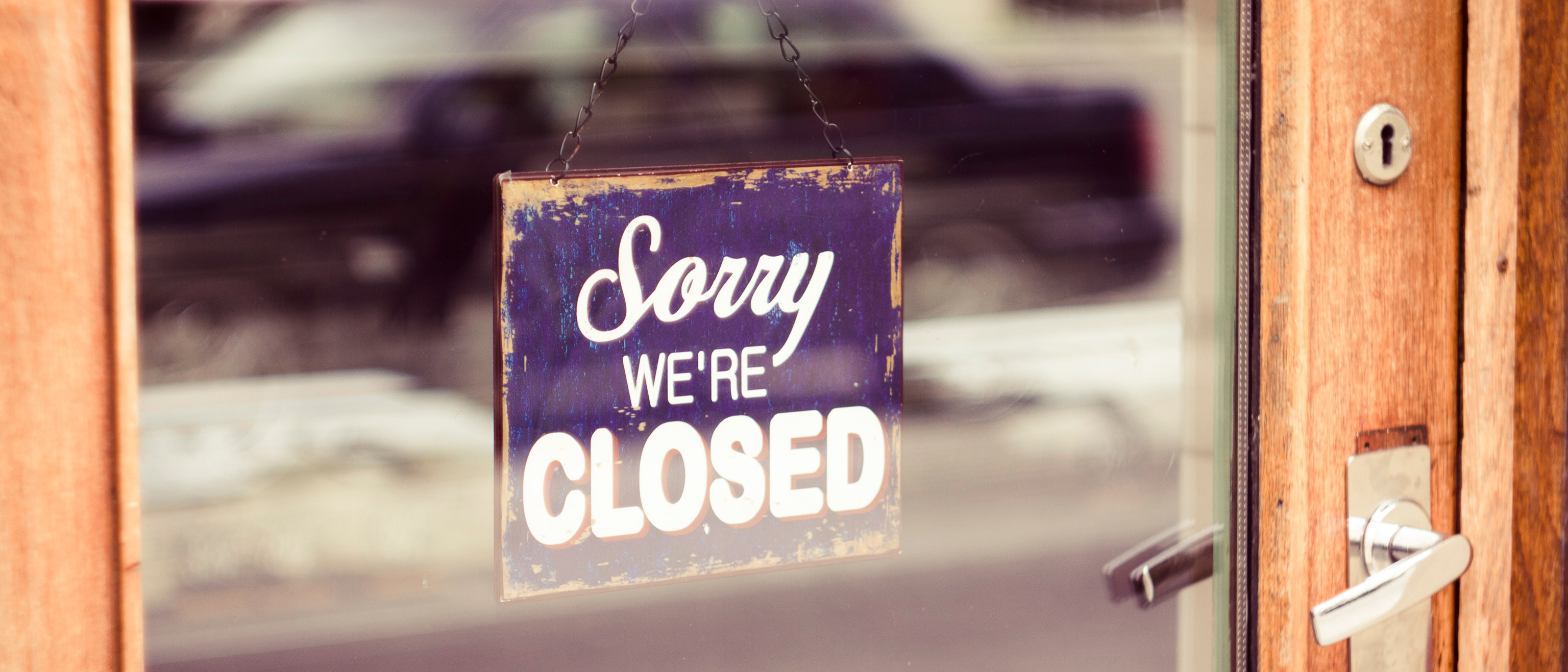 Sorry we're closed sign hung on the store's entrance door