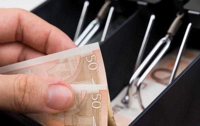 Photo d'un caissier volant de l'argent dans la caisse.