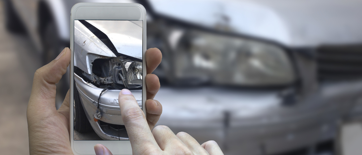 Person taking a photo with phone of a car damaged in accident