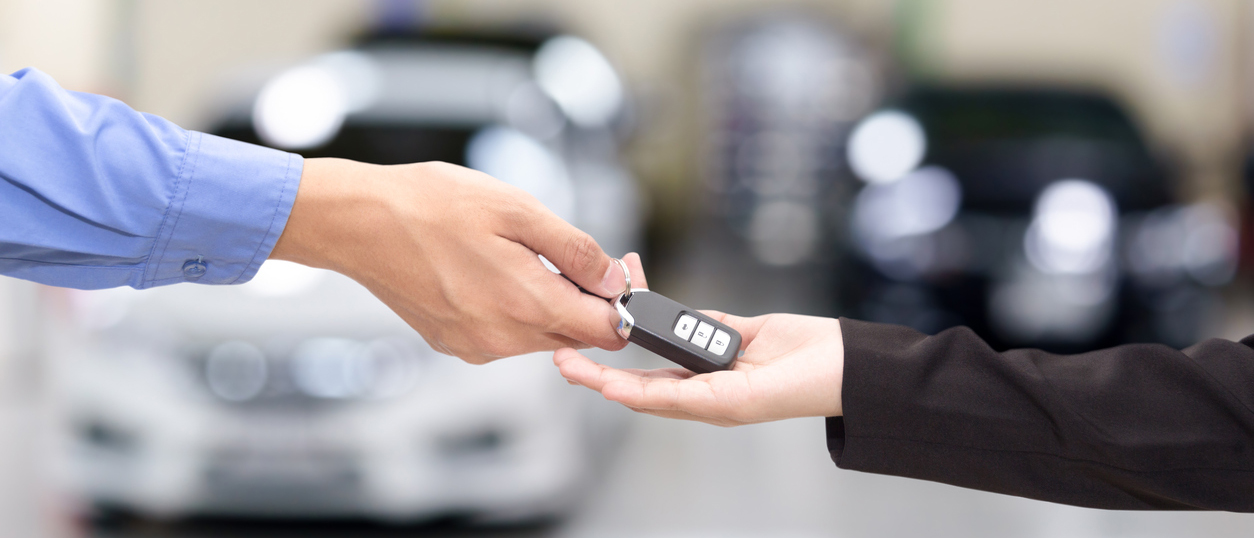 Business owner giving car keys to someone else to lend them their company car