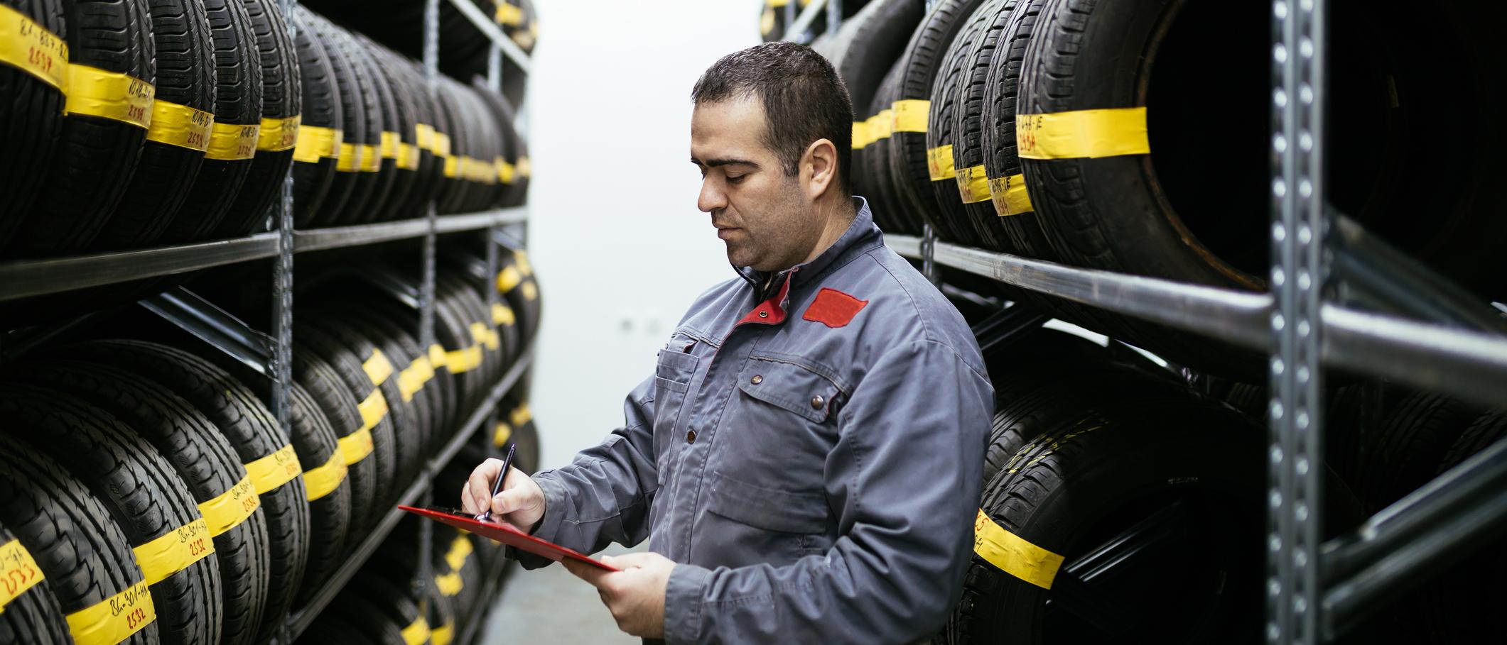 Photo d'un mécanicien automobile vérifiant si les pneus sont entreposés de façon sécuritaire dans un entrepôt.