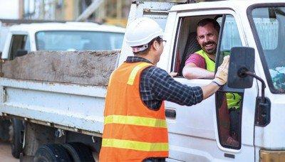 Photo d'un camionneur discutant joyeusement avec un travailleur sur un chantier.