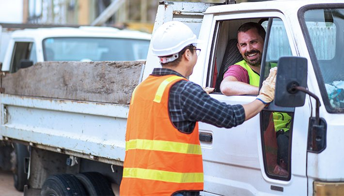Truck driver happily conversing with construction work on site