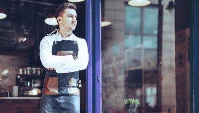 Photo d'un propriétaire d'entreprise se tenant debout devant sa boutique.