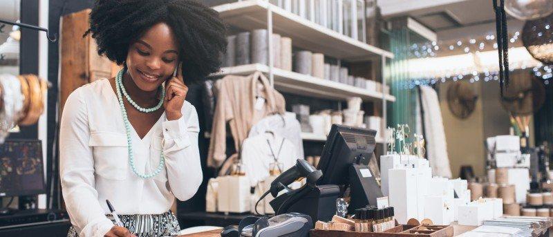 Photo d'une propriétaire d'un magasin de détail parlant au téléphone en souriant.