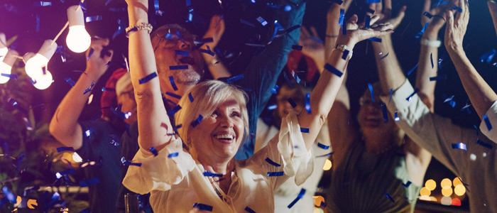 woman with hands up and blue confetti falling down