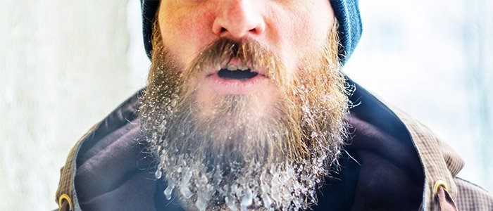 man breathing out cold air with frost on his beard