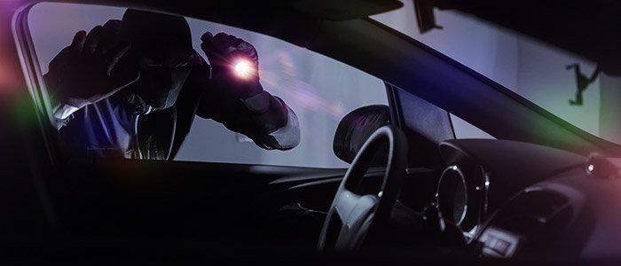 Homme portant un masque noir et regardant dans un véhicule à l'aide d'une lampe de poche.