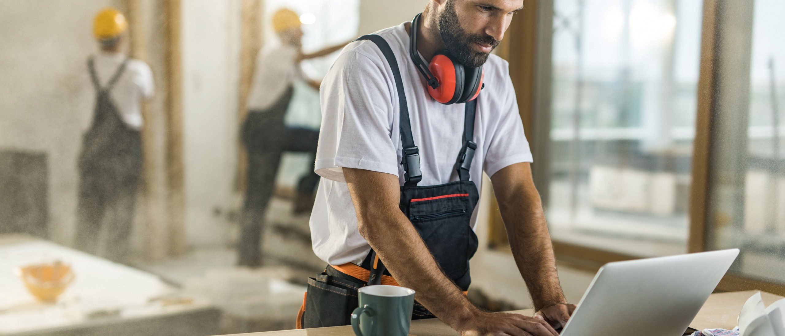 male contractor using a laptop at a construction site