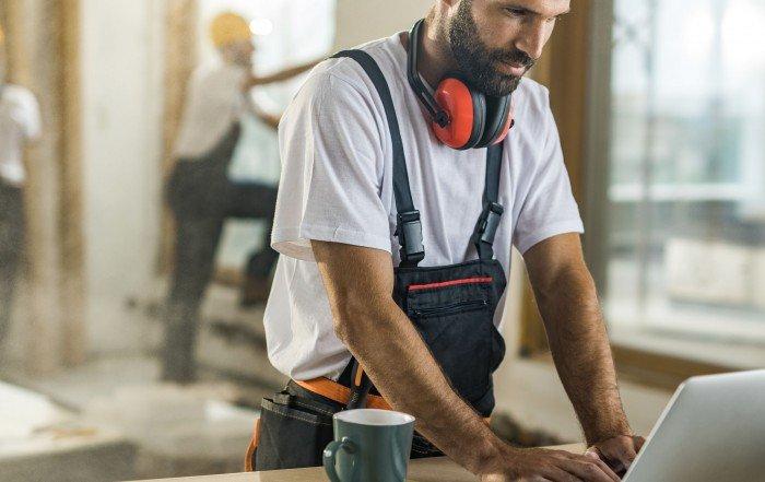 entrepreneur tapant à son ordinateur portatif sur un chantier de construction
