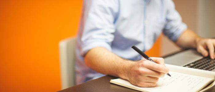 Homme d'affaires assis dans un bureau orange travaillant sur un plan d'affaires